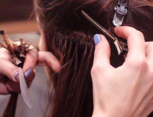 Die Echthaar-Extensions beim Friseur einarbeiten zu lassen, kann je nach Extensions-Methode ins Geld gehen.