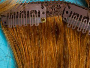 Clip-in-Extensions aus Echthaar halten mit Metallklammern im Haar.