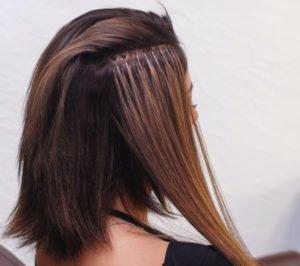 Bei einer brasilianischen Haarverlängerung werden Echthaar-Strähnen mittels Fäden ins Eigenhaar eingearbeitet.